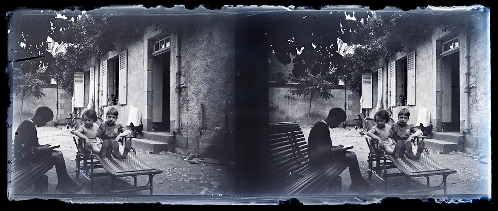 children resting and reading a book outside in front of the home France 1920s