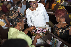 3 November 2019, Monrovia, Liberia: Bread and wine is distributed during Sunday service at the Providence Baptist Church, also known as 'the cornerstone of the nation', as it was in the Providence Baptist Church that Liberia's declaration of independence was signed. While this Sunday service is taking place in a larger worship space finalized in 1976, the old chapel remains in place adjacent to the new one, and is still in use.