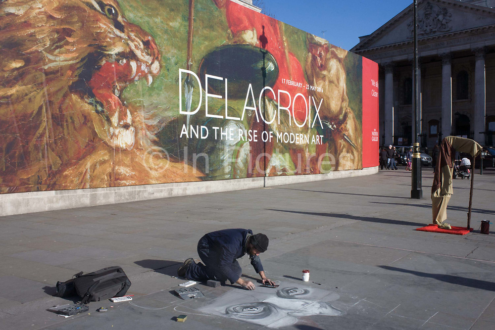 In front of the broad message on a hoarding announcing the next major exhibition by Eugène Delacroix at the National Gallery in London, a street artist draws a classical face on the pavement in Trafalgar Square. Kneeling down on the pavement of this landmark in central London, we see the juxtaposition of classical art and the everyday version of street sketching. In the background we also see a busker dressed as iconic Star Wars character, Yoda. Ferdinand Victor Eugène Delacroix (1798 – 1863) was a French Romantic artist regarded from the outset of his career as the leader of the French Romantic school