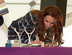 The Duchess of Cambridge signs a photo for a time caspsule as she visits the National Graphene Research Institute during a day of engagements in Manchester.