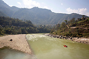 An inflatable boat carrying tourists calmly floating down the Trishuli river on the 3rd of March 2020 near Malekhu Benighat region, Nepal. White water rafting is common with tourists on the Trishuli river due to stunning views,  impressive gorges and exciting rapids, the river is one of the major tributaries of the Narayani River basin in central Nepal.