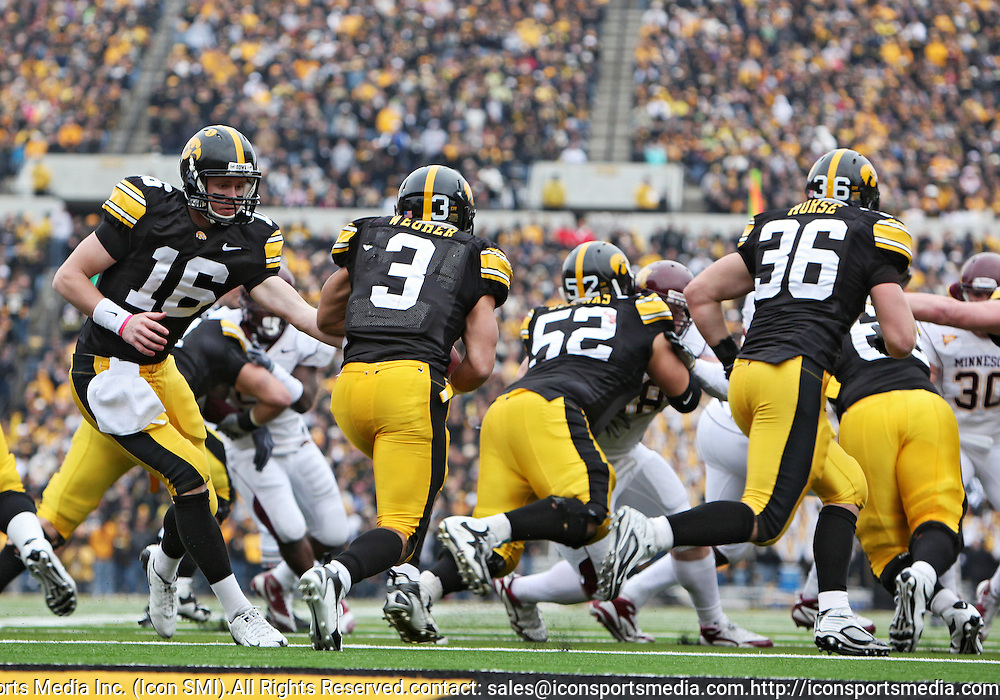 November 21, 2009: Iowa quarterback James Vandenberg (16) hands the ball off to Iowa running back Brandon Wegher (3) in their own end zone during the second half of the Iowa Hawkeyes 12-0 win over the Minnesota Golden Gophers at Kinnick Stadium in Iowa City, Iowa on November 21, 2009.