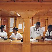 INDIVIDUAL(S) PHOTOGRAPHED: From left to right: Louisseul Sanchez Mirlène, Jean Jacques Jacqueline, Laurent Wesner Junior, and Singha Pierre Antoine. LOCATION: Justinian University Hospital (HUJ), Cap-Haïtien, Haïti. CAPTION: Medical students Louisseul Sanchez Mirlène, Jean Jacques Jacqueline, Laurent Wesner Junior, and Singha Pierre Antoine discuss patient records in the Women's General Medicine Department at Justinien University Hospital (HUJ) in Cap-Haïtien.
