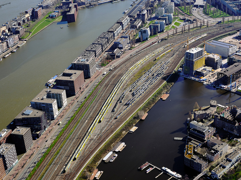 """Nederland, Noord-Holland, Amsterdam; 23-03-2020; Piet Heinkade met emplacement van de NS (Rietlanden). Oostelijke eilanden met IJhaven en Veemkade, Dijksgracht (rechts).<br /> Door de Coronacrisis is er weinig verkeer en omdat de NS een speciale basisdienstregeling ingevoerd, zijn veel treinen 'geparkeerd' op opstelsporen. <br /> Piet Heinkade with railway yard of the NS (Rietlanden). Eastern islands with IJhaven and Veemkade, Dijksgracht (right).<br /> Due to the Corona crisis, there is little traffic and because the NS has introduced a special basic timetable, many trains are """"parked"""" on Railway yard.<br /> <br /> luchtfoto (toeslag op standaard tarieven);<br /> aerial photo (additional fee required)<br /> copyright © 2020 foto/photo Siebe Swart"""