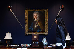 """© Licensed to London News Pictures. 23/03/2017. London, UK.  A staff member views Scottish basket-hilted broadswords, said to be that carried by Alexander, 4th Lord Forbes of Pitsligo (Est. GBP1,200-1,500), which are hanging next to a """"A Portrait of Alexander, 4th Lord Forbes of Pitsligo"""" by Alexis-Simon Belle (Est. GBP15-20k).  Preview at Sotheby's New Bond Street of property from two great Scottish families, the Forbeses of Pitsligo and the Marquesses of Lothian, which will be auctioned in London on 28 March.   Photo credit : Stephen Chung/LNP"""