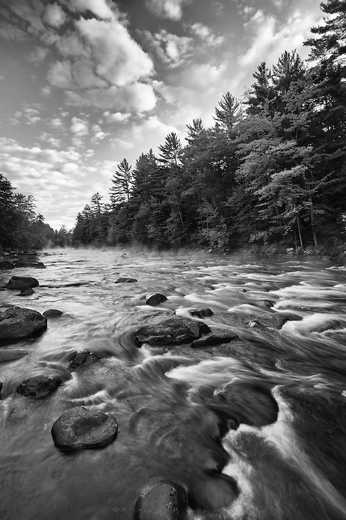 Schroon River, Adirondacks, NY.<br /> This river has always been a favorite of mine.  It begins quite some distance north of here and is impounded in Schroon Lake before continuing it's journey to meet the Hudson down around Thurman.  I fished it for many years before photographing it, and it is for much of the year, a big and dangerous river that gives up nice trout.  Back in the day I even caught landlocked salmon in here.  The bottom is strewn with slick boulders ranging from the size of a football  to a riding lawnmower, and you can go from knee deep to neck deep in a step.  It is intense wading.  It makes for some challenging photography as well.  Summer drought allowed me to rock hop out quite a ways a bit above a river bend, where I could get out for a vantage point not usually there, into the rapids.  The sky had been more solid and not not very promising on this morning. But as the sun rose, it began to break up-- a nice counter to the river, itself breaking into white water a short ways above me, and the fingers of mist giving it up as the air warmed.