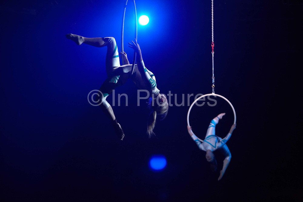 Circus acrobats perform high above auditor Ernst & Young's staff during a company Academy Day held for 3,000 of their London employees at Excel in London's Docklands England. Lit with blue light by powerful spotlights, the two girls are suspended in mid-air using hoops attached to safety ropes. They both make dramatic shapes in the air to demonstrate confidence, synchronised teamwork and co-operation between partners, the themes of this corporate day out of the office. The employees out of sight below are attending this fair where motivational pep-talks from executives, outside speakers and gurus will talk to large groups of E & Y personnel so their presence on this day away from the office is vital for the year's business ahead.