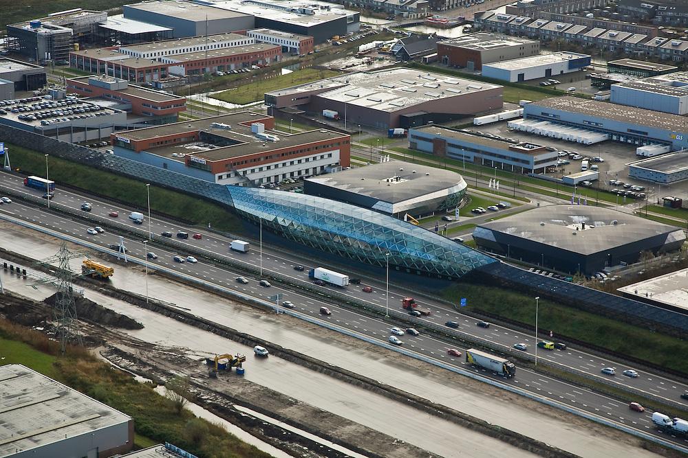 Nederland, Utrecht, Leidsche Rijn, 25-11-2008; autosnelweg A2 ter hoogte van Lage Weide, verbreding naar 2x5 rijstrokennaast de snelweg het monumentale geluidsscherm, .met 'de cockpit' (het druppel-vormig gebouw), autoshowroom voor luxe automobielen van Hessinghet geluidsscherm is 1500 m lang en bestaat uit een vakwerkconstructie van staal en glas (architect Oosterhuis)A2 motorwaynear Utrecht, widening to 2x5 lanes of highway A2next to the road a monumental noise barrier (sound screen), with the cockpit (the drop-shaped building), car showroom for luxury automobiles of Hessing, the sound screen is 1,500 m long and consists of a lattice structure of steel and glass (architect Oosterhuis)auto showroom.  .luchtfoto (toeslag)aerial photo (additional fee required).foto Siebe Swart / photo Siebe Swart