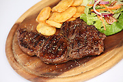 Grilled steak on wooden platter with fried potato and salad