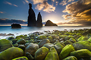 Green stones beach and giant rocks in the ocean at sunrise