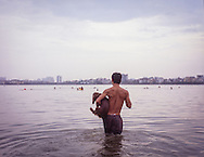 Shirtless man holds a small dog as he wades into West Lake in Hanoi, Vietnam, Southeast Asia