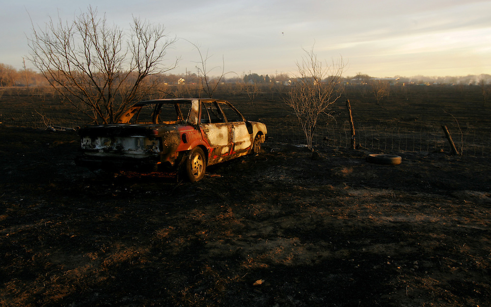 © 2005 Alex Jones www.alexjonesphoto.com..A car sits burned in a field on Wednesday, December 28, 2005 in Cross Plains, Texas.  The town was heavily damaged by an uncontrolled grass fire on Tuesday, one of many in the state.