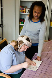 Day service user with learning disability watching her colleague draw,