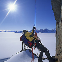 ANTARCTICA, Queen Maud Land. Mike Graber ascends rope on overhanging cliff on Rakekniven spire, Filchner Mountains.