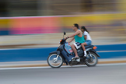 Mexico, Yucatan, Isla Mujeres (Island of Women), people on scooter (blurred motion)