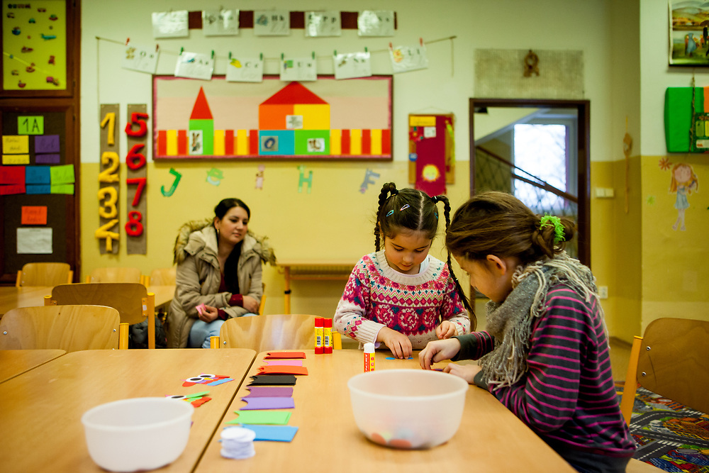 Esther Kroscenova (6) with her mother Daniela Kroscenova (27) in the back waiting for an enrollment examination (test) of daughter Esther who should be a first class pupil in the school year 2016/2017 in a mainstream school in the city of Ostrava, where Roma and non Roma children are educated together. The school is named ZS Chrustova elementary school. The girls are doing some handicraft during waiting for the test. (NO signed MODEL RELEASE for the girl on the right)