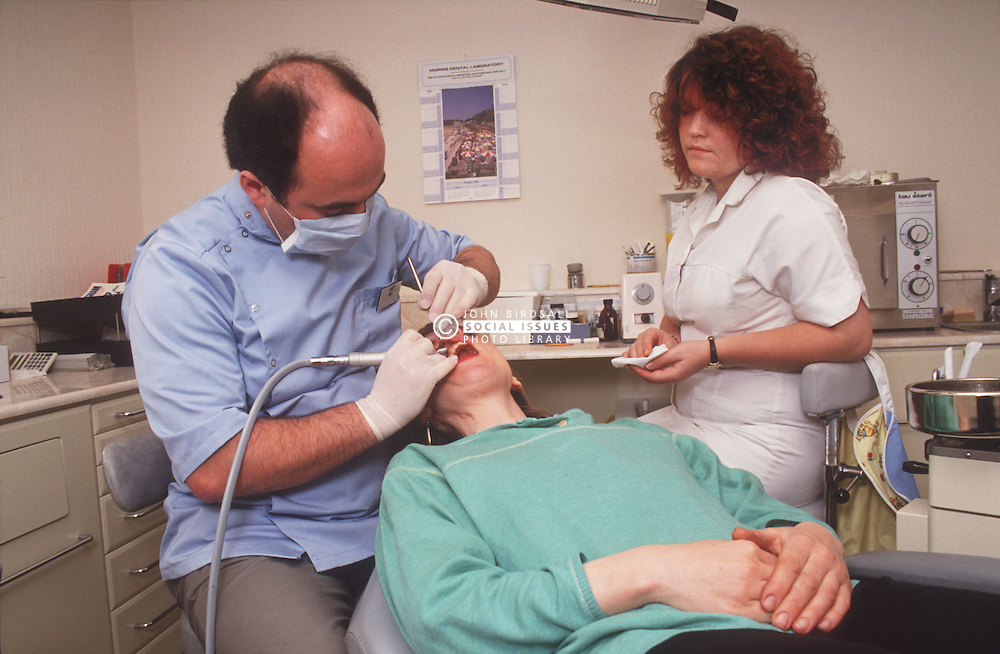 Dentist at work cleaning patient's teeth with assistance of dental nurse,