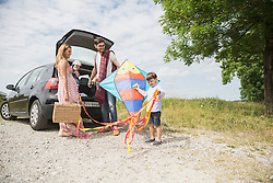 Family with kite unloading the car on meadow in the countryside, Bavaria, Germany