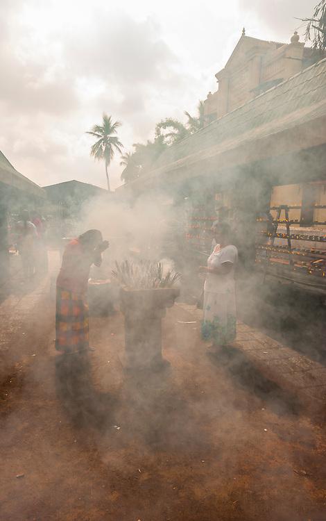 Buddhist Pilgrims lighting incense sticks outside the Sri Maha Bodhi. The sacred bodhi tree. Anuradhapura, North Central, Sri Lanka.