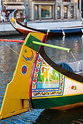 Traditional brightly painted gondola style moliceiro canal boat with saucy scenes painted on prow in Aveiro, Portugal