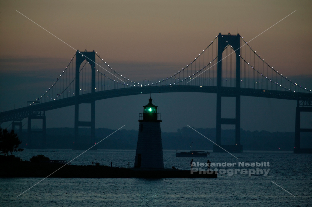 USA, Newport, RI - Sunset fades over two men at goat Island Green light with Newport Bridge behind, motor yacht Pam is in the distance.