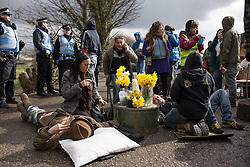 © Licensed to London News Pictures . 21/03/2014 . Barton Moss , Manchester , UK . Two men lock themselves together using concrete and metal pipes and lie in the middle of the road down which lorries from the iGas site need to pass . The Barton Moss anti-fracking demonstration camp today (Friday 21st March 2014) . Photo credit : Joel Goodman/LNP