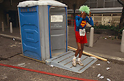 Taking a break from the London Marathon, a young runner dressed as Superman emerges from a Portaloo after a quick toilet stop. Located at the London Fire Brigade's station on Lower Thames Street in City of London in the capital's historic financial district, their empty fire hose snakes across the ground. The young man wears trainers, a red skirt, a Super-hero top with the Superman emblem on his chest and he walks out of the portable convenience adjusting a green frizzy wig. Disgarded mineral water bottles have been thrown on the ground by other passing athletes but this is a theatrical pun, that Superman changes personality, name and powers when leaving a telephone box. Apart from the colour (color) of the toilet, the runner and the hose, the background is drab and overcast.  The City of London has a resident population of under 10,000 but a daily working population of 311,000. The City of London is a geographically-small City within Greater London, England. The City as it is known, is the historic core of London from which, along with Westminster, the modern conurbation grew. The City's boundaries have remained constant since the Middle Ages but  it is now only a tiny part of Greater London. The City of London is a major financial centre, often referred to as just the City or as the Square Mile, as it is approximately one square mile (2.6 km) in area. London Bridge's history stretches back to the first crossing over Roman Londinium, close to this site and subsequent wooden and stone bridges have helped modern London become a financial success.