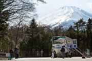 A snow-capped Mount Fuji above the  a parked Yamanakako Hippo Bus (Kaba bus) at Lake Yamanaka Yamanashi, Japan. Thursday March 26th 2020. This amphibious  bus takes tourists on two hour tours around and on Lake Yamanaka, one of the Fuji five lakes.