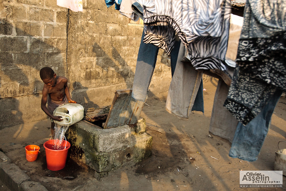 A boy draws water from a well in the West Point slum in Monrovia, Montserrado county, Liberia on Monday April 2, 2012.