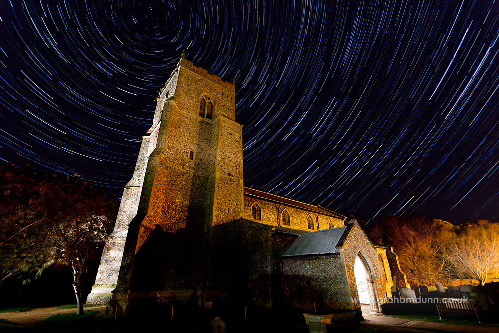 Star trail above Brancaster Church. The North Star is positioned above the church tower. North Norfolk, East Anglia.