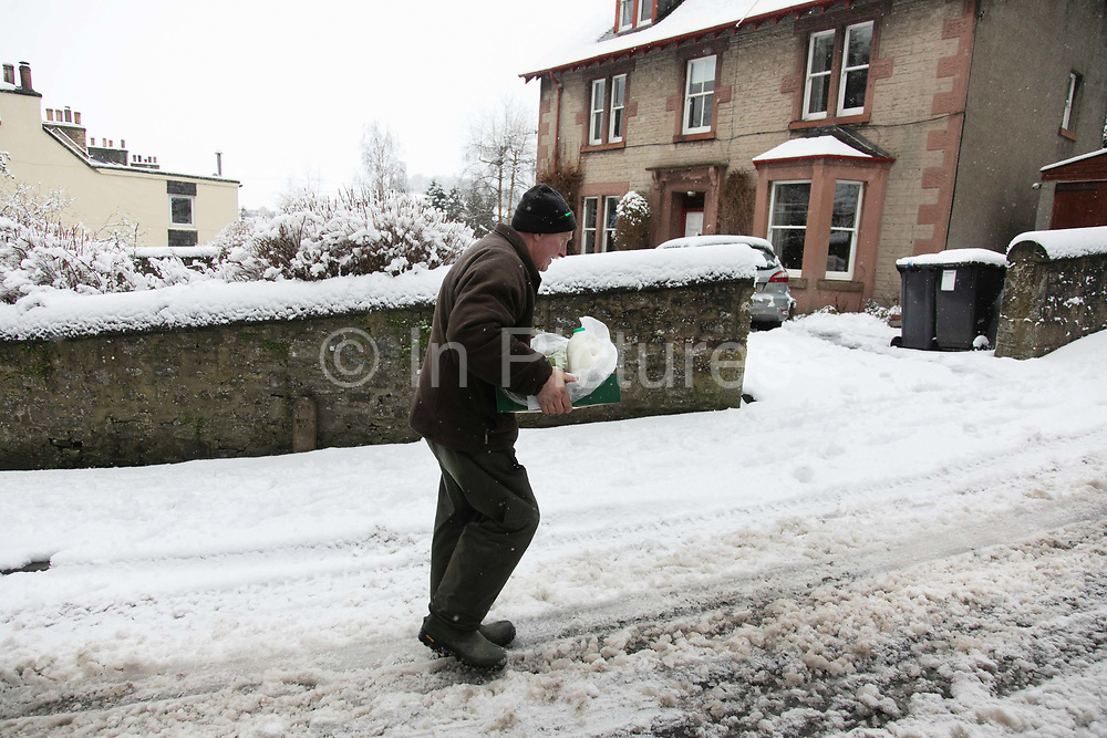 Gordon Anderson delivers fresh milk and vegetables to a local resident on 14th of January 2021 in Stow, Scottish Borders, United Kingdom. Gordon Anderson runs a fresh milk and vegetables delivery service with his wife and they deliver to local houses and farms in and around the village of Stow. The first real snow of the year has been falling all night and morning and the village is covered in fresh snow.
