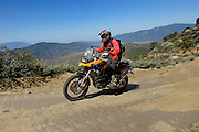 BMW F800GS motorcycle traveling along dirt road in Mojave desert in California