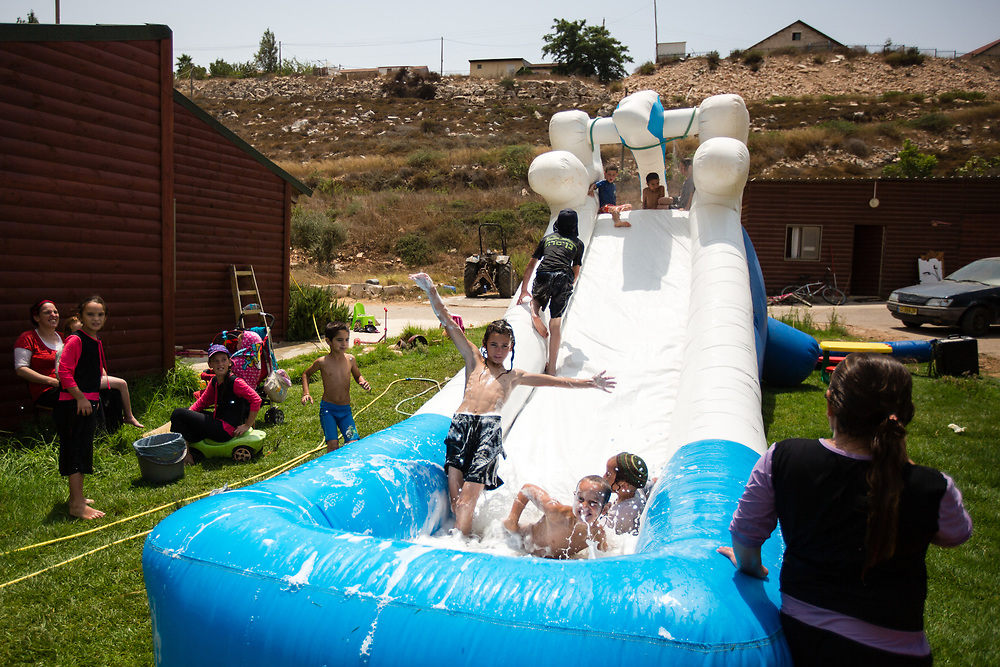 Jewish Israeli children slide down an inflatable water slide, during a hot summer day in the West Bank Jewish settlement of Yitzhar, south of the Palestinian West Bank city of Nablus, on August 5, 2015.