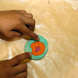 Austin,TX 17 FEB 2005: After-school 4H science program for 4th and 5th grade Hispanic students, Hispanic fingers pressing out cross-section model of the earth's layers from modeling clay. ©Bob Daemmrich