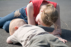 Older sister looking after her younger brother after a fall,