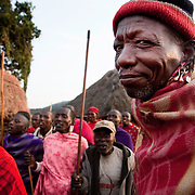 Wilson's wedding day...It is not just the young men who do the dancing, small groups of men and women dance around the village in between the huts, - here one of the elders at Wilson's party is enjoying the spectacle.. .It is mainly Maasais who live in the Loita Hills up above the Serengeti plains. They live in small villages and communities called bomas and live mainly of raising and selling live stock such as cattle and goats. Its a very remote region in Kenya, hard to get to without a four wheel drive with very little infrastructure and up till 2010 no mobile phone network. The Maasais are well known though out Kenya and the world for their colorful clothing and their way of keeping their old traditions alive.