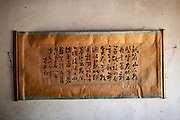A handwritten, Chinese calligraphy sign hanging in a calligrapher's shop in Shaxi, Yunnan Province, China.