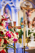 A flowered cross with the reredos and statue depicting Jesus Christ, seen on Monday, April 5, 2021, at Immanuel Lutheran Church, St. Charles, Mo. LCMS Communications/Erik M. Lunsford