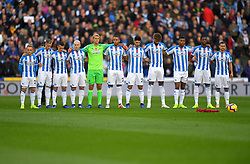 Huddersfield Town layers line up for a minutes silence for Armistice Day behind a poppy wreath and football ahead of the Premier League match at the John Smith's Stadium, Huddersfield.