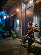 """27 JANUARY 2016 - BANGKOK, THAILAND: One of the house musicians tunes his """"Saw Duang,"""" a two stringed Thai violin, in front of Tep Bar, a new bar and restaurant in the Chinatown neighborhood of Bangkok.       PHOTO BY JACK KURTZ"""
