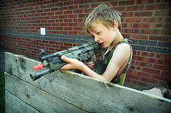 Nine year old boy playing with toy gun, Leicestershire, England, UK.