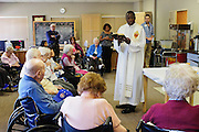 Rev. Paula Maina Waithaka celebrates mass with residents at The Abbington of Glenview healthcare residence on Wednesday, August 20th. Waithaka is Pastor at St. Catherine Laboure in Glenview. August 20th, 2014 l Brian J. Morowczynski-ViaPhotos<br /> <br /> For use in a single edition of Catholic New World Publications, Archdiocese of Chicago. Further use and/or distribution may be negotiated separately. <br /> <br /> Contact ViaPhotos at 708-602-0449 or email brian@viaphotos.com.