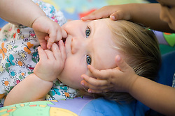 Toddler lying down; her friends touching her head; at Nursery School,