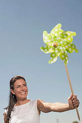 Happy woman with paper windmill at geothermal power station, Bavaria, Germany