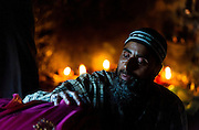 """9th April 2015, New Delhi, India. A Sufi 'pir' (master) bestows the baraka (the blessing of Allah) in the form of 'dam' (breath in Arabic) on a female supplicant at a shrine dedicated to Djinn worship in the ruins of Feroz Shah Kotla in New Delhi, India on the 9th April 2015<br /> <br /> PHOTOGRAPH BY AND COPYRIGHT OF SIMON DE TREY-WHITE a photographer in delhi<br /> + 91 98103 99809. Email: simon@simondetreywhite.com<br /> <br /> People have been coming to Firoz Shah Kotla to leave written notes and offerings for Djinns in the hopes of getting wishes granted since the late 1970's. Jinn, jann or djinn are supernatural creatures in Islamic mythology as well as pre-Islamic Arabian mythology. They are mentioned frequently in the Quran  and other Islamic texts and inhabit an unseen world called Djinnestan. In Islamic theology jinn are said to be creatures with free will, made from smokeless fire by Allah as humans were made of clay, among other things. According to the Quran, jinn have free will, and Iblīs abused this freedom in front of Allah by refusing to bow to Adam when Allah ordered angels and jinn to do so. For disobeying Allah, Iblīs was expelled from Paradise and called """"Shayṭān"""" (Satan).They are usually invisible to humans, but humans do appear clearly to jinn, as they can possess them. Like humans, jinn will also be judged on the Day of Judgment and will be sent to Paradise or Hell according to their deeds. Feroz Shah Tughlaq (r. 1351–88), the Sultan of Delhi, established the fortified city of Ferozabad in 1354, as the new capital of the Delhi Sultanate, and included in it the site of the present Feroz Shah Kotla. Kotla literally means fortress or citadel."""