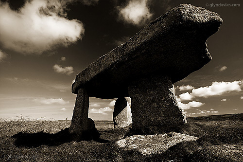 In the early 19th Century, the capstone was rotated, and the uprights altered to support it. In the process the quoit was lowered considerably. It was said that originally a horse and rider could pass comfortably beneath it. It may originally have been as long as 60 feet in length and is estimated to have been erected in 2500 BC.  In the background stands the famous Ding Ding Mine, where Cornish miners toiled hard to extract tin for world export. It's ironic that whilst we were pulling out precious metals we were simultaneously sinking ancient monuments !