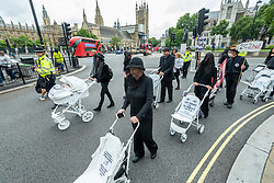 """© Licensed to London News Pictures. 31/08/2021. LONDON, UK.  Climate activists from Extinction Rebellion pushing prams painted white, walk from Parliament Square to Trafalgar Square to highlight the effects of climate change on children and to urge the government to stop fossil fuel funding.  The event takes place on day nine of the two week 'Impossible Rebellion' protest to """"target the root cause of the climate and ecological crisis""""..  Photo credit: Stephen Chung/LNP"""