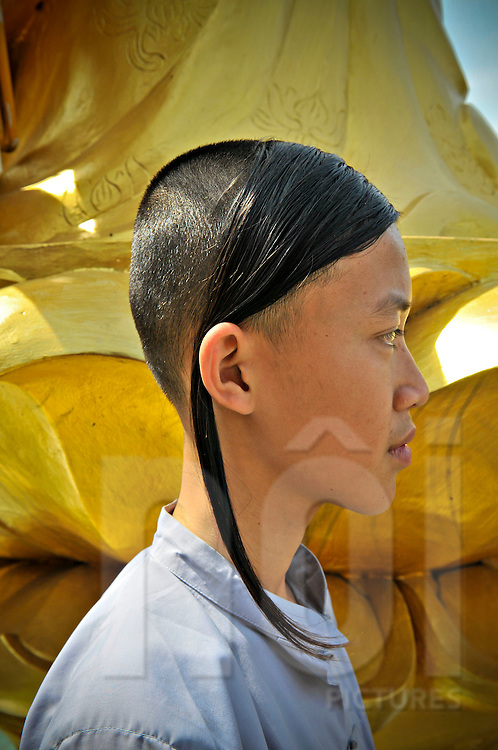 Profile of a young Buddhist monk standing in fron of a statue, Khanh Hoa Province, Vietnam, Southeast Asia