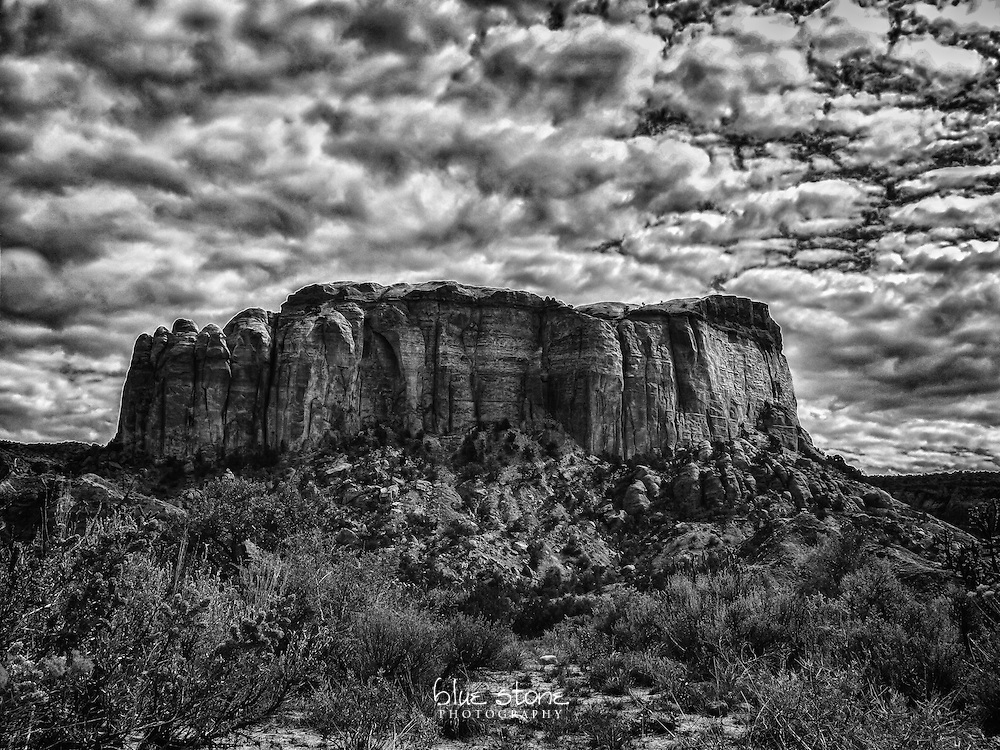 Black and white photograph of a granite outcrop near Ghost Ranch that is set against the clouds with desert grasses and cacti.<br /> <br /> Wall art is available in metal, canvas, float wrap and standout. Art prints are available in lustre, glossy, matte and metallic finishes.