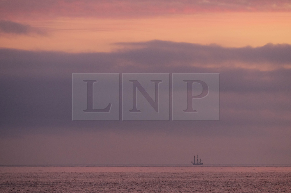 © Licensed to London News Pictures. <br /> 18/08/2016. <br /> Satburn-By-The-Sea, UK.  <br /> <br /> A ship sails along the horizon as the sun begins to rise over Saltburn-By-The-Sea.<br /> <br /> Photo credit: Ian Forsyth/LNP
